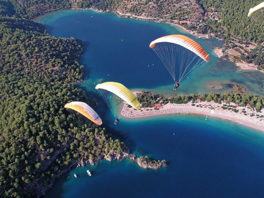 Drei Gleitschirme fliegen über Wasser