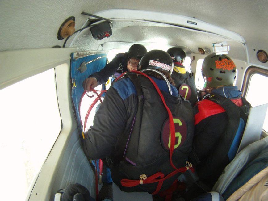 Ein paar Fallschirmspringer in einem Flugzeug, die sich auf den Sprung vorbereiten