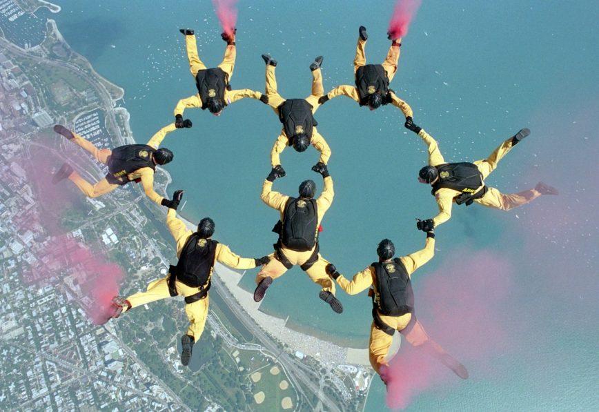 Ein Team von Fallschirmspringern in gelben Anzügen macht ein geometrisches Muster am Himmel, indem sie sich aneinander halten