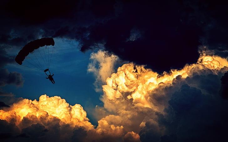 Ein Fallschirmspringer, der am Himmel in der Nähe großer Wolken schwebt