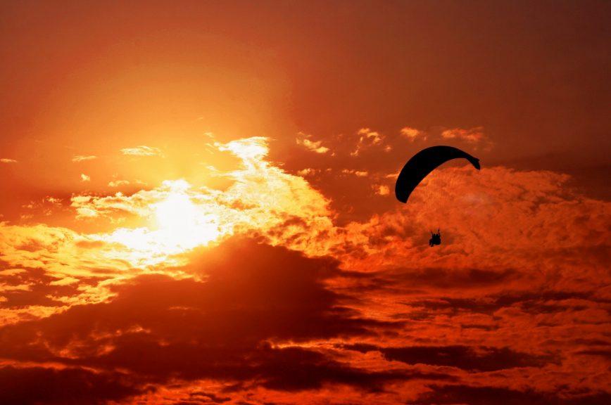 Ein Gleitschirm, der während des Sonnenuntergangs fliegt
