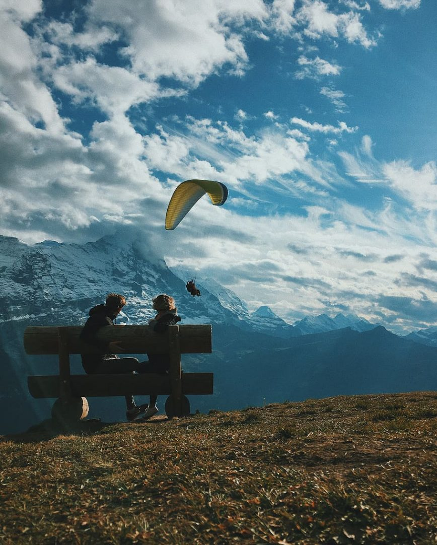 Ein Paar sitzt auf einer Bank und beobachtet einen Gleitschirm, der über die Berge fliegt