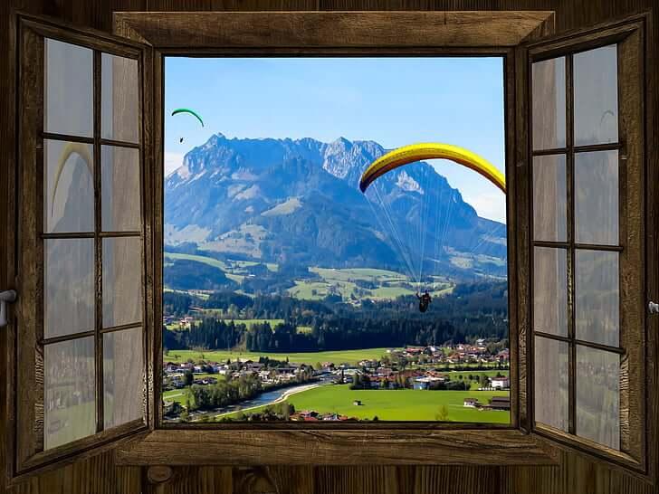 Fensterausblick, Berge und Menschen, die über die Berge Gleitschirmfliegen