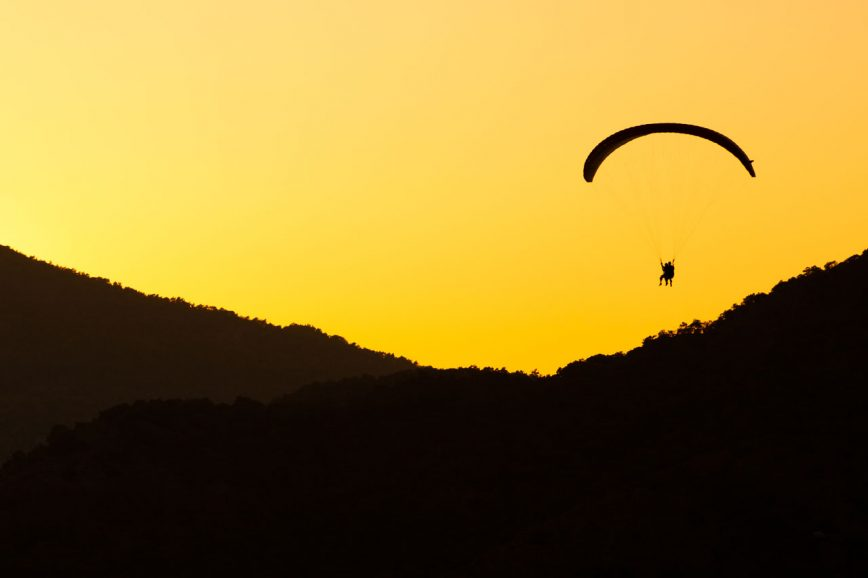 Ein Tandem-Gleitschirm fliegen bei Sonnenuntergang