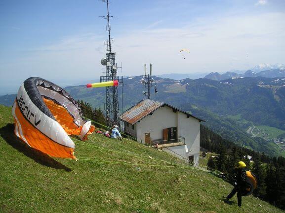 Eine Person, die sich auf den Start mit einem Gleitschirm von einem Bergfeld vorbereitet, kleines Haus im Hintergrund
