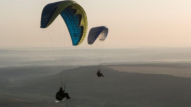 Zwei Gleitschirme fliegen über Felder