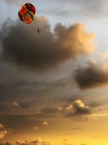 Eine Person Parasailing in einem Himmel mit riesige orange Wolken