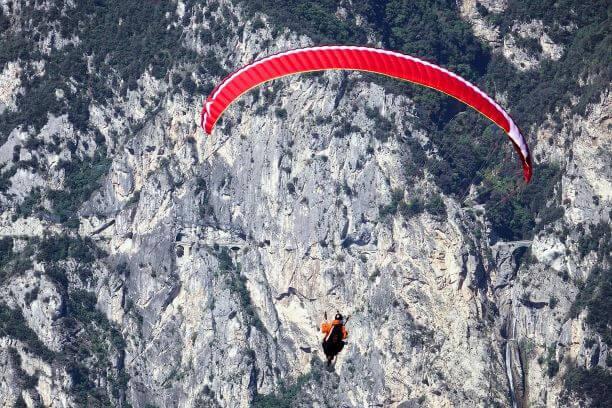 Ein roter Gleitschirm gleitet in der Luft über einem felsigen Berg