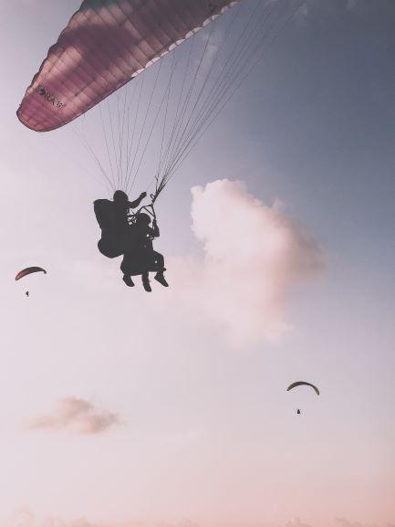 Die Silhouetten von zwei Personen, die im Tandem Gleitschirmfliegen und zwei anderen Gleitschirmen in der Ferne
