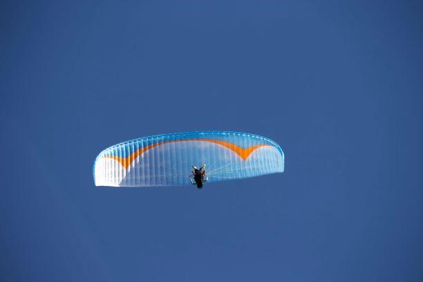 Ein Gleitschirmflieger am Himmel, von unten abgebildet