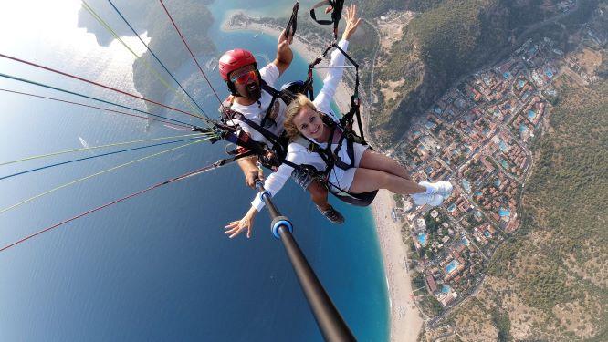 Tandem Gleitschirmflieger, die glücklich aussehen, während sie über einer Stadt in der Türkei fliegen, der Pilot hält einen Selfie-Stock