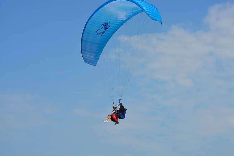 Tandem Paragliding Duo, das durch einen klaren blauen Himmel gleitet