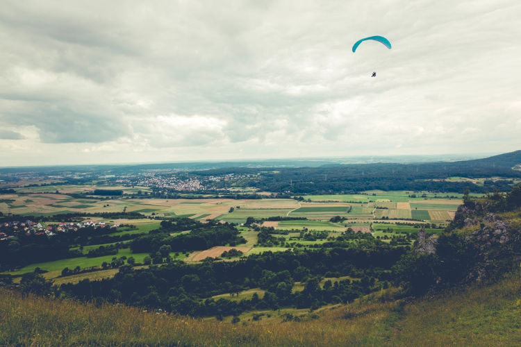 Ein blauer Gleitschirm fliegt über grünem Land