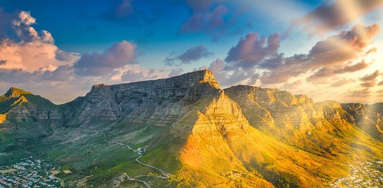Ein Berg, auf einer Seite von der Sonne beleuchtet, Kapstadt am Fuße des Berges