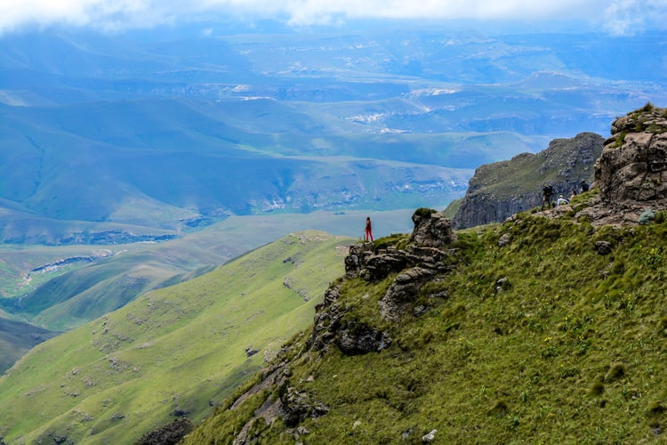 Eine Frau, die am Rand einer Klippe steht und die grüne Berge in Drakensberg in Südafrika betrachtet
