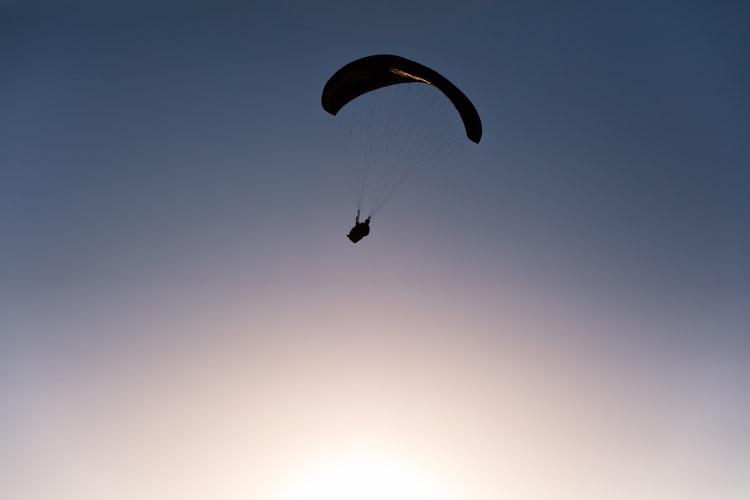 Eine Silhouette eines Gleitschirms in einem dunkelblauen Himmel