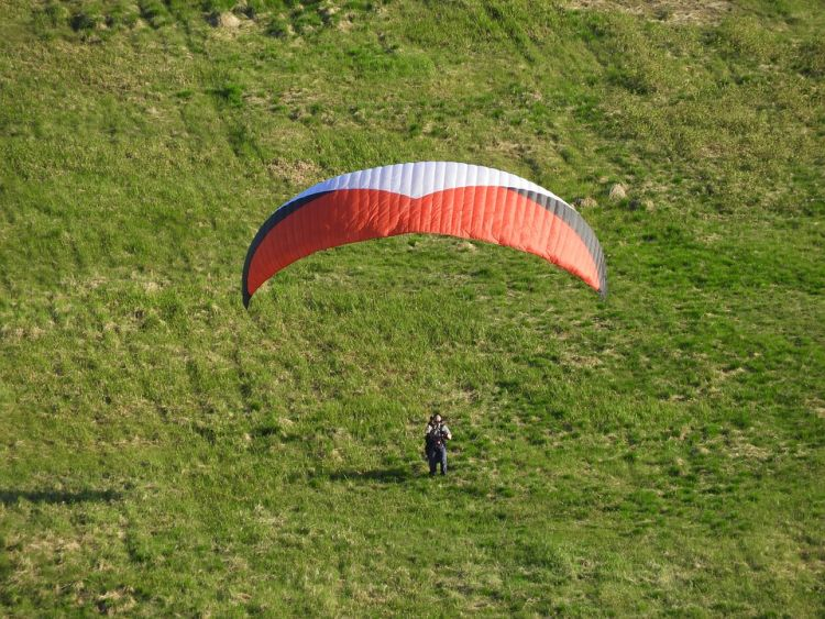 Eine Person mit einem weißen und roten Gleitschirm auf einem grünen Hügel