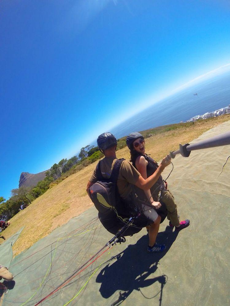 Ein Mann und eine Frau bereiten sich auf den Start mit einem Gleitschirm vor, die Frau macht ein Foto mit einem Selfie-Stick