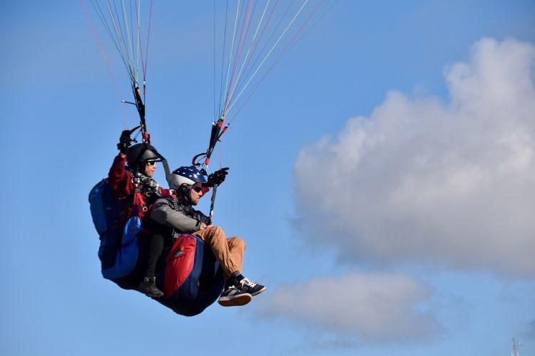Zwei Tandem-Gleitschirmflieger sitzen in einem Baldachin-Flügel und schweben in der Luft