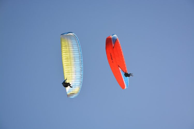 Zwei Gleitschirmflieger fliegen nahe beieinander am Himmel