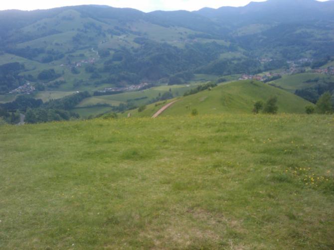 Im Vordergrund die Startfläche, direkt die Kuppe dahinter ist der Top-Landeplatz. Der eigentliche Landeplatz ist ganz unten im Tal die Wiede im Dreieck zwischen den Bäumen. Aufgenommen am 26.5.2010 von mir.