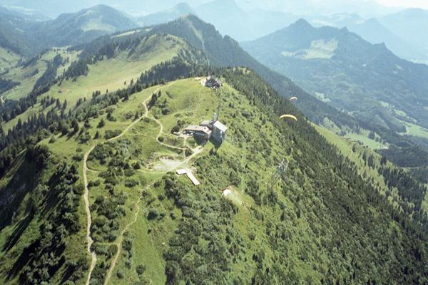 Gipfel der Hochries von Osten, vor dem Gipfelhaus (östlich) befindet sich die Drachen-Startrampe, rechts (unterhalb) der Gleitschirm-Startplatz