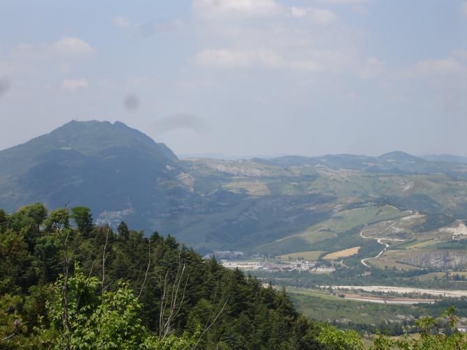 Blick von San Leo aus zu Talamello. Gestartet wird auf der Schulter rechts des Berges, nicht am Gipfel.  Der Landeplatz ist vomBetrachter aus gesehen vor dem Industriegebiet.